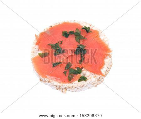 Smoked wild pacific sockeye salmon with parsley on organic brown rice cake isolated on white background