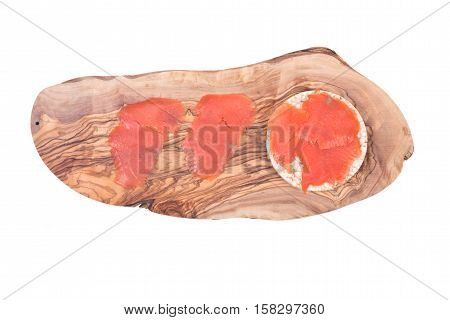 Smoked wild pacific sockeye salmon on organic brown rice cake and olive wood cutting board isolated on white background