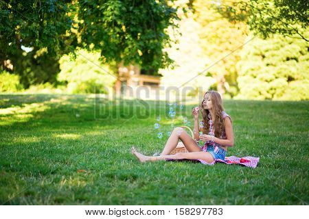 Girl Blowing Bubbles In Park