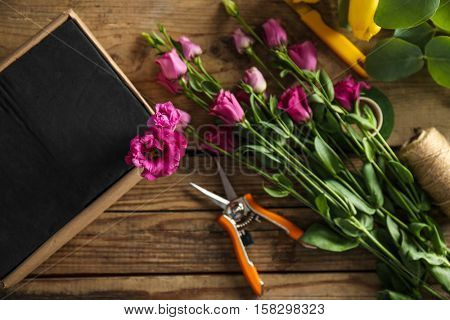 Beautiful flowers with box and florist equipment on wooden background