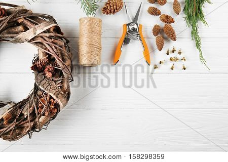 Decorative wreath and florist equipment on white wooden background
