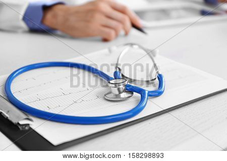 Clipboard, stethoscope and cardiogram on doctor table
