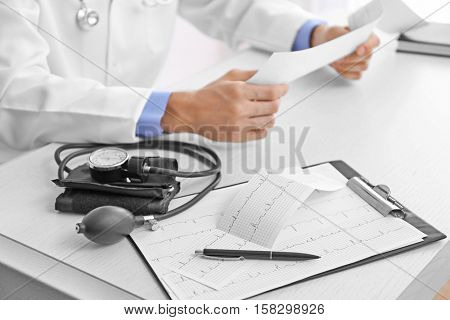 Clipboard, sphygmomanometer, pen and cardiogram on doctor table