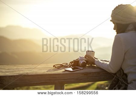 Woman drinking coffee in sun sitting outdoor in sunshine light enjoying her morning coffee soft and select focus