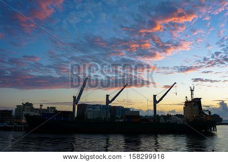 Labuan,Malaysia-Jan 22,2016:Silhouette of container vessel unloaded in Labuan port during sunrise at Labuan,Malaysia.Its a sheltered deep water harbour which is an important transshipment point.
