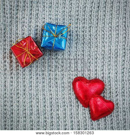Closeup macro texture of grey knitted wool fabric material shawl scarf background withtwo red candies hearts on top and red and blue gift boxes presents Valentine holiday card love romance concept