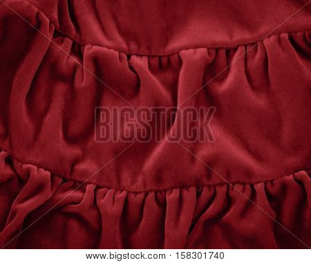 Closeup macro texture of modern red crimson burgundy marsala color fleece fabric clothing background with wrinkles and folds luxury royal trendy