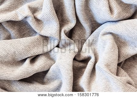 Closeup macro texture of knitted cotton waffle fabric clothing background with wrinkles and folds