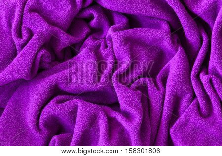 Closeup macro texture of pink violet purple fleece fabric clothing background with wrinkles and folds