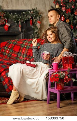 Loving couple and Christmas. Girl hugging boyfriend. She is holding a cup with hot drink on Christmas. In the background a beautiful Christmas tree.
