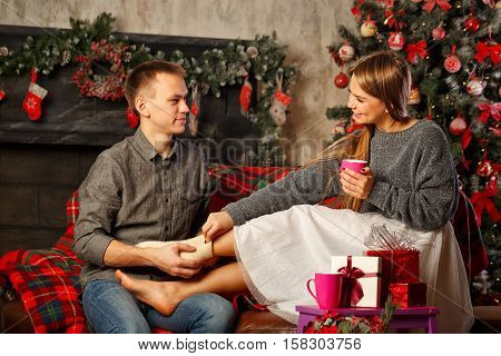 Loving couple and Christmas. Boyfriend wears woolen knit socks on the feet of his girlfriend. In the background a beautiful Christmas tree. Homeliness