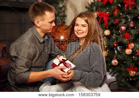 Loving couple and Christmas. Man gives a girl a Christmas gift. They sit on the floor near the fireplace. They are happy. In the background a beautiful Christmas tree.