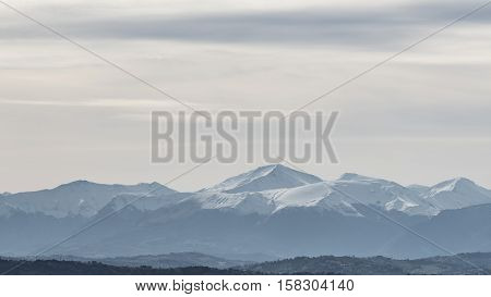 winter panorama with snow-capped mountains range  and cloudy sky