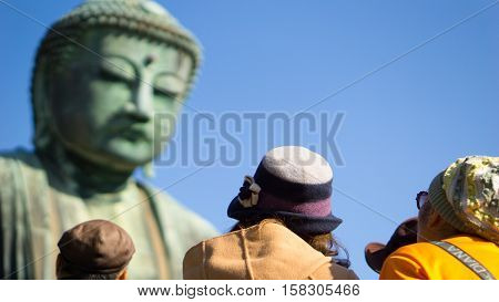 japan travel and asian tourist concept - Close up back side of asian tourist looking daibutsu buddha statue in kotoku in temple Kamamura japan