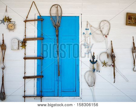 Beach fishing decoration in a white wall with blue window