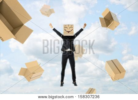 A businessman wears a box on his head with a funny face painted on it, lifts his hands up like being happy and empty boxes flying away from him on a sky background. Business success. Face masks. Hidden emotions.