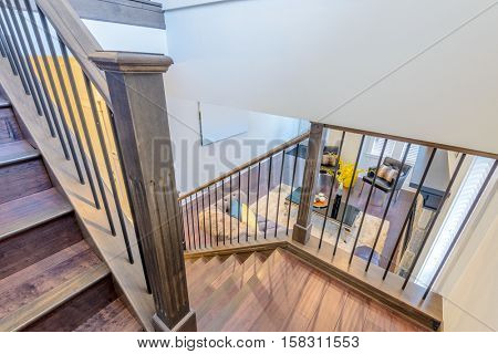 Beautiful living room interior with hardwood floors and vaulted ceiling in new luxury home. View of stairs, and second story loft style area