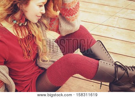 Young slim woman model dressed in warm knitted stockings and knee-high boots, hand made necklace, outdoor fashion portrait, soft vintage color