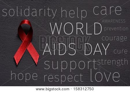 a red ribbon for the fight against AIDS, the text world aids day and some other words relative to it, like hope, help, care, support or awareness, on a dark gray surface
