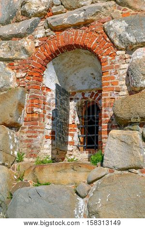 A fragment of the old wall with window and bars. City architecture exterior