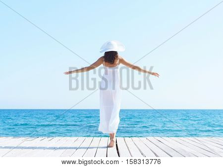 Woman in white dress on a wooden pier on summer.  Sea and sky background. Vacation, traveling and freedom concept.