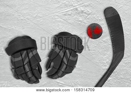 Canadian hockey puck stick and gloves on the ice. Concept