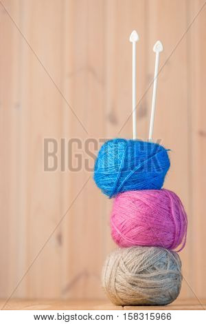 Skeins Of Wool Yarn And Knitting Needles On A Wooden Table Close-up