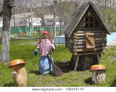 A fairy house of unmarried old witch with a wooden leg in the summer garden on a green lawn.