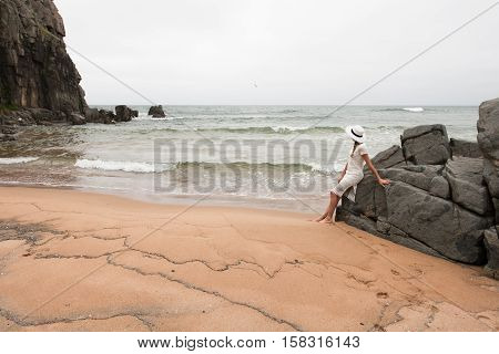 Lonely slender woman on a deserted beach on the background of large stones and a cloudy sky.