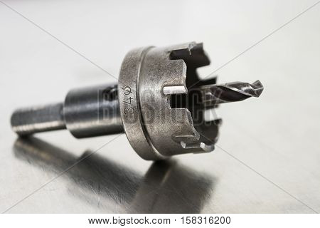 Close up steel drill bit on stainless steel background.