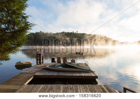 Early morning sun rises over the dock on the narrows on Lake of Bays in Muskoka