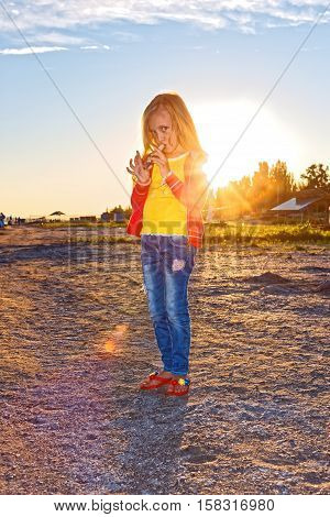 Little girl standing on the beach and playing the flute at sunset