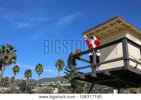 Santa Claus Life Guard. Santa Lifeguard. Santa Claus is a lifeguard at the beach in a lifeguard tower outside.