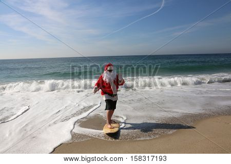 Surfing Santa. Santa Claus Surfs on his Surf Board while on a Beautiful Beach with a Blue Ocean. Focus on Santa/s Face. Santa Vacation. Surfing Santa. Santa goes Surfing. Santa Claus enjoys the beach