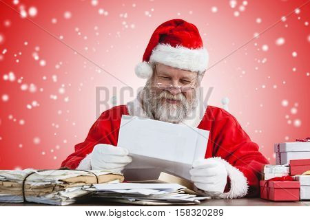 Cheerful Santa Claus reading letter against white light dots on red