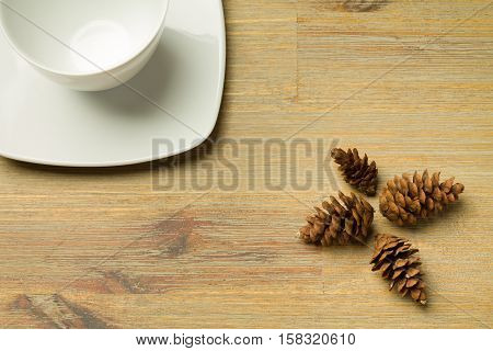 Four brown cones aligned in a cross shape and a white cup on a office desk with empty copyspace. Background, nature, forest, conifers. cofee, cup