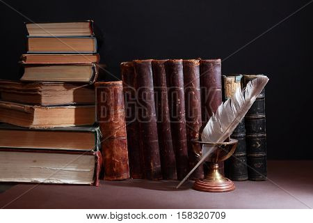 Vintage library. Feather against set of old book in a row