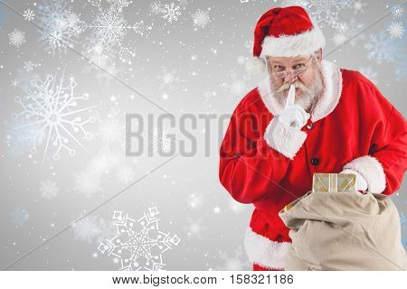 Santa Claus with finger on lips and holding gifts against snowflake pattern