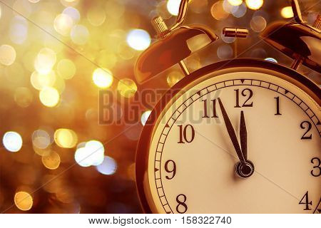 vintage alarm clock is showing midnight. It is twelve o'clock christmas and bokeh holiday happy new year festive concept on light bokeh background