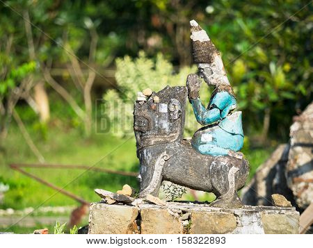 Broken religious figurine at Ratana Man Aung a pagoda in Mrauk U the Rakhine State of Myanmar. Shallow depth of field with the figurine in focus.
