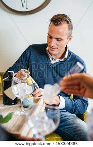 Young man making gin tonic cocktails at party with friends.