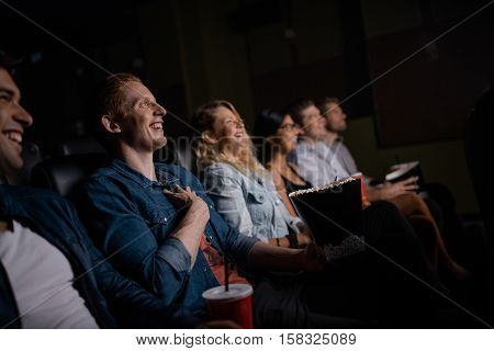 Group of friends sitting in multiplex movie theater with popcorn and drinks. Young people watching movie in cinema hall.