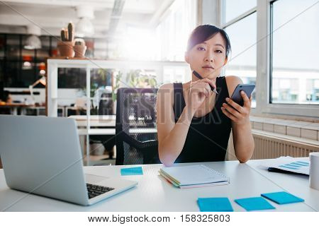 Portrait of confident asian woman sitting at her desk with mobile phone. Asian businesswoman working in office.