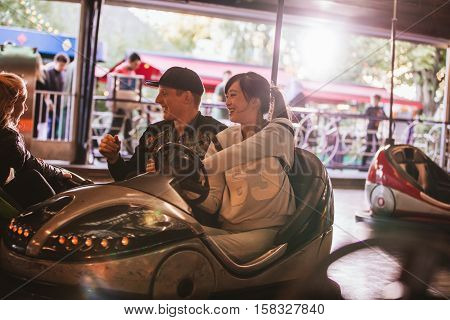 Friends on bumper car ride in amusement park. Young man and woman having fun with bumper cars at fairground.
