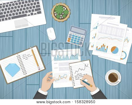 Man analyzes documents. Accounting, analytics, market analysis, report, research, planning concept. Hands on the desktop hold documents. Charts, diagrams, graphs on the paper. Office space top view.