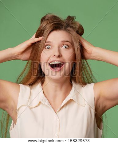 Girl shows elation, his hair disheveled, his hands in his head. Eyes, mouth wide open, isolated on white background. Good mood, good luck, emotion - happiness.