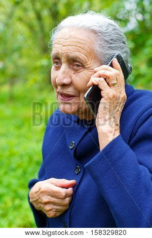 Portrait of a happy elderly woman while talking on cell phone