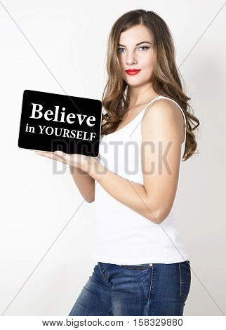 believe in yourself written on virtual screen. technology, internet and networking concept. beautiful woman with bare shoulders holding pc tablet.