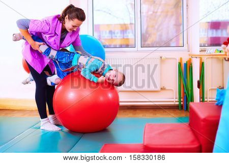 Cute Kid With Disability Has Musculoskeletal Therapy By Doing Exercises In Body Fixing Belts On Fit