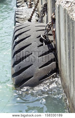 Old lorry tyres used as protection for boats at a harbor quayside